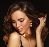 Bello modello della donna con l'acconciatura riccia che indossa gioielli eleganti fotografia stock