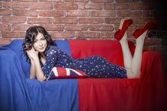 Bello modello della donna sul sofà nel vestito nella t blu e rossa Immagini Stock