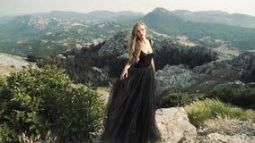 Bello modello della giovane donna in un vestito lungo elegante lanuginoso nero che posa sulla macchina fotografica nei precedenti archivi video