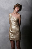Bello modello della ragazza del ritratto in un vestito lussuoso dall'oro Immagine Stock