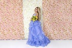 Bello modello della sposa in vestito da sposa stupefacente blu Giovane donna di bellezza sui precedenti dei fiori - immagine fotografie stock libere da diritti