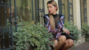 Bello modello di lusso alla moda della donna che posa seduta vicino all'esterno della costruzione archivi video
