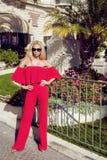 Bello modello di moda femminile elegante in vestito rosso che sta davanti agli alberghi di lusso ed ai boutique Immagini Stock Libere da Diritti