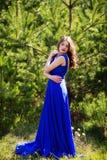Bello modello di moda in un vestito in un parco verde di estate Vestito blu fotografia stock libera da diritti