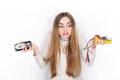 Bello modello femminile biondo emozionale che sembra drive del hard disk e multimetro rotti tenuta confusa Fotografia Stock