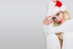 Bello modello femminile biondo sexy vestito come Santa Claus in uno spiritello malevolo Immagini Stock Libere da Diritti