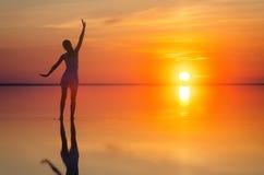 Bello modello femminile a braccia aperte nell'ambito di alba alla spiaggia L'acqua calma del lago di sale Elton riflette la silue Immagini Stock Libere da Diritti