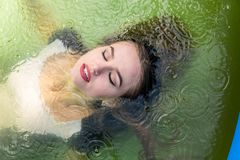 Bello modello femminile vestito in vestiti da sera lunghi, nelle bugie nello stagno e sensuale nelle pose immagini stock