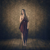 Bello modello nel fondo di seta rosso dell'annata e del vestito Immagine Stock
