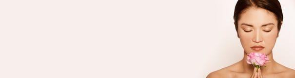 Bello modello Smelling Pink Rose di panorama immagini stock
