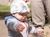 Bello neonato che gioca sul campo da giuoco con sua madre È vestito in una bici leggera Fotografia Stock