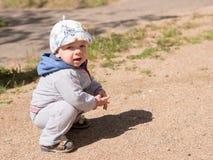 Bello neonato che gioca sul campo da giuoco con sua madre È vestito in una bici leggera Fotografia Stock Libera da Diritti