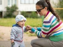 Bello neonato che gioca sul campo da giuoco con sua madre È vestito in una bici leggera Fotografie Stock