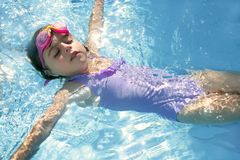 Bello nuoto della ragazza sul raggruppamento blu Fotografia Stock Libera da Diritti