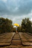 Bello ombrello di giallo della tenuta della donna e camminare su un vecchio ponte nella campagna sotto la pioggia fotografie stock libere da diritti