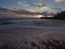 Bello ond di tramonto la riva di mare della spiaggia di sabbia con arenaria cli fotografia stock