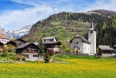 Bello paesaggio alpino con la chiesa e le case svizzere tipiche al giorno soleggiato della molla, villaggio di Inden, cantone del Fotografie Stock