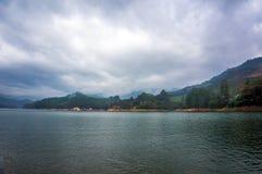Bello paesaggio con il lago della montagna in mezzo delle alte montagne con le piantagioni di tè ed il cielo della nuvola Fotografia Stock Libera da Diritti