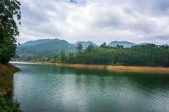 Bello paesaggio con il lago della montagna in mezzo delle alte montagne con le piantagioni di tè ed il cielo della nuvola Fotografia Stock