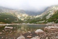 Bello paesaggio con il lago e la nebbia della montagna Immagini Stock
