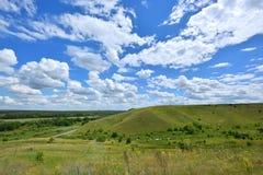 Bello paesaggio con una collina verde e un cielo blu con le nuvole Fotografia Stock