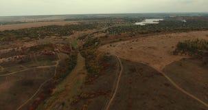 Bello paesaggio Contaminazione regolare su un quadrocopter Campagna con fuori strada Lago in mezzo alle colline ed ai campi stock footage