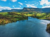 Bello paesaggio del lago, dei campi verdi e delle montagne immagine stock