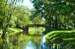 Bello paesaggio del parco con il fiume ed il ponte Fotografie Stock Libere da Diritti