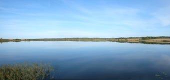 Bello paesaggio della campagna con il lago, le colline e la foresta lontano nel giorno di estate Immagini Stock