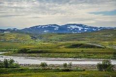 Bello paesaggio della collina coperto di erba e di montagna parzialmente coperte di neve dalla città di Alta, Norvegia Fotografie Stock Libere da Diritti