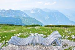 Bello paesaggio della montagna con cielo blu, banco sulla priorità alta e la gente su fondo colorful Alpi austriache immagine stock