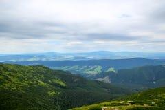 Bello paesaggio della montagna con erba alta e pietre su un fondo di cielo blu e delle nuvole Fotografia Stock Libera da Diritti