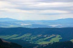Bello paesaggio della montagna con gli alberi verdi sul fondo del cielo blu Immagine Stock