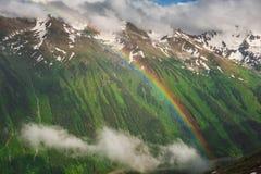 Bello paesaggio della montagna con l'arcobaleno e le nuvole Fotografia Stock
