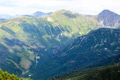 Bello paesaggio della montagna con vegetazione sui precedenti di cielo blu Fotografia Stock