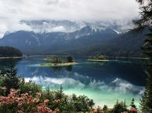 Bello paesaggio della montagna del lago alpino Eibsee, contro il contesto della montagna Zugspitze coperto di nebbia immagine stock