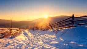 Bello paesaggio della montagna di inverno alla luce molle di tramonto, alberi glassati lungo il percorso nevoso immagini stock libere da diritti