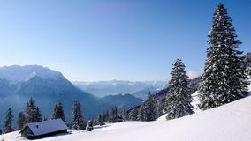 Bello paesaggio della montagna di inverno con un cottage e una foresta e una grande vista dietro Immagini Stock