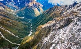 Bello paesaggio della Nuova Zelanda - colline coperte da erba verde di montagne vigorose coperte da neve dietro Fotografie Stock
