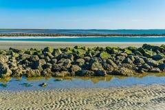 Bello paesaggio della spiaggia con una linea di rocce impilate fotografia stock