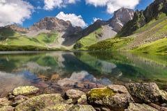 Bello paesaggio di estate Lago della montagna dello specchio ed alte rocce Fotografie Stock Libere da Diritti