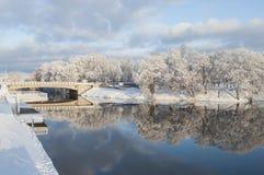 Bello paesaggio di inverno con il ponte e riflessione piacevole in acqua del fiume Fotografia Stock