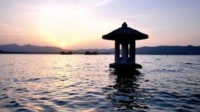 Bello paesaggio di tramonto lago ad ovest, Hangzhou, in Cina, cielo arancio di crepuscolo ed acqua pacifica con i padiglioni trad archivi video