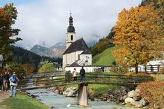 Bello paesaggio di un ponte di legno sopra una corrente davanti ad una chiesa con le montagne nebbiose nei precedenti Fotografie Stock