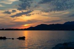 Bello paesaggio ispiratore di tramonto in mare e le montagne Fotografie Stock