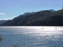 Bello paesaggio montagnoso con un lago che riflette la luce solare in Argentina Immagini Stock