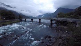 Bello paesaggio norvegese nella sera con il fiume ed il ponte vicino alla città di Odda norway video d archivio