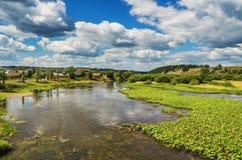 Bello paesaggio rurale con il fiume e le nuvole Fotografia Stock