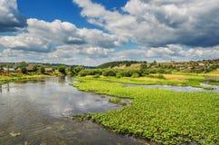 Bello paesaggio rurale con il fiume e le nuvole Fotografia Stock Libera da Diritti