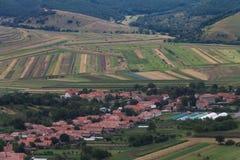Bello paesaggio rurale del villaggio di Coltesti e dei campi variopinti in montagne di Apuseni Fotografie Stock Libere da Diritti